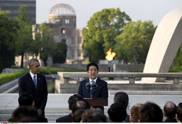 U.S. President Barack Obama, left, looks to Japanese Prime Minister Shinzo Abe as he speaks during a ceremony at the cenotaph at Hiroshima Peace Memorial Park in Hiroshima, western, Japan, Friday, May 27, 2016. Obama on Friday became the first sitting U.S. president to visit the site of the world's first atomic bomb attack, bringing global attention both to survivors and to his unfulfilled vision of a world without nuclear weapons. Atomic Bomb Dome is seen in the background. (AP Photo/Carolyn Kaster)  /OTKCK126/753952204211/ /1605281947