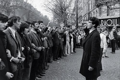 Les étudiants manifestent avant l'intervention de la police au carrefour du boulevard Saint-Michel et du boulevard Saint-Germain, à Cluny, avec pour leader Alain Krivine des Jeunesses Communistes Révolutionnaires. On remarquera le caractère très bourgeois de ces manifestants. Politique magazine